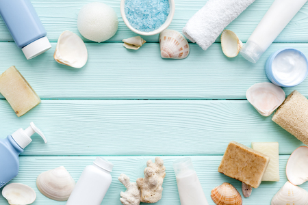 spa organic cosmetics, cream, lotion, bath salt, soap with Dead Sea minerals and shells on mint green wooden desk background flat lay space for text