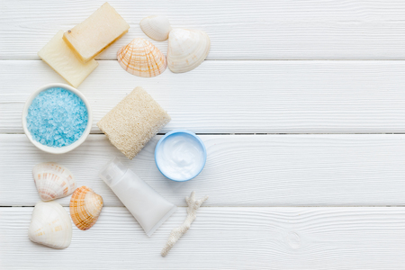Skin care concept. Cosmetics with Dead Sea minerals. Cream, lotion, salt, soap and shells on white wooden table background top view copy space