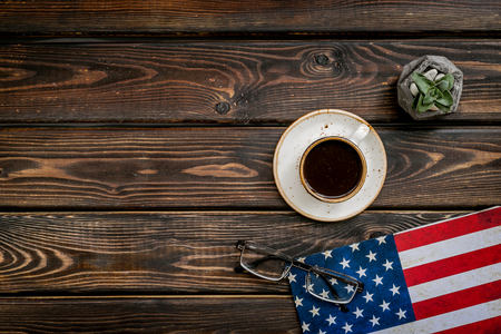 Symbol of Independence. USA national day background with flag and cup of coffee on wooden desk top view copy space Фото со стока