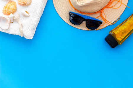 Travel to the seaside. Straw hat, sun glasses, shells and sunblock cream for sea vacation on blue background top view copy space