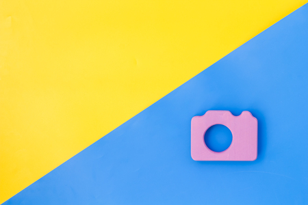 Photo camera concept on yellow and blue background top view mock up.