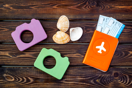 Travel to the seaside. Funny vocation concept with camera, passport and tickets on wooden background top view