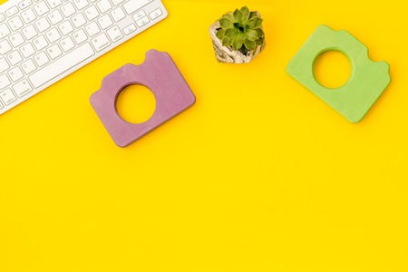 Office desk of blogger with photo camera, keyboard and plant on yellow background top view copy space