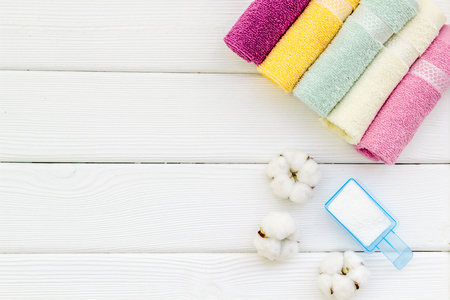 Washing of cotton products. Powder for laundry and cotton towels on white wooden background top view mockup