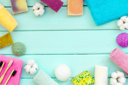 Soap, tooth brush, bath bomb and cotton towels for body care and washing frame on mint green wooden desk background top view mockup Фото со стока