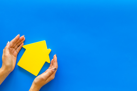 New house purchase. Property insurance concept with house toy in hands on blue background top view mock up Фото со стока