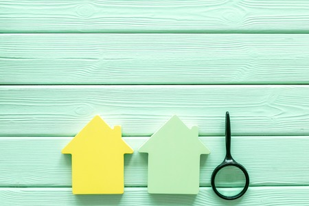 Purchasing a new property on credit. Mortgage credit concept with house toy and magnifier on mint green wooden background top view copy space