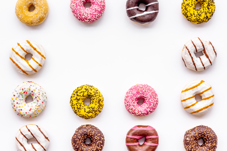 Sweet break concept. Traditional american donuts of different flavors on white background flat lay pattern Фото со стока