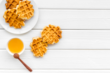 Homemade bakery. Breakfast with Belgian waffles with honey and spoon on white wooden table background top view mockup