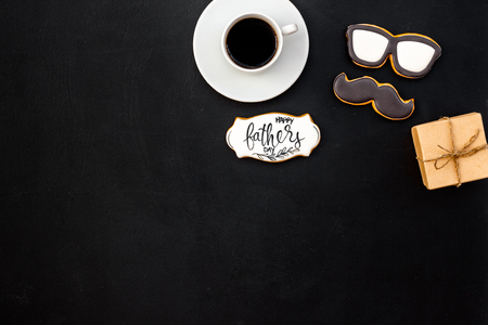 Moustache, glasses figures. Design for Father Day celebration party with cookies, gift box and coffee on black background top view mock up Фото со стока