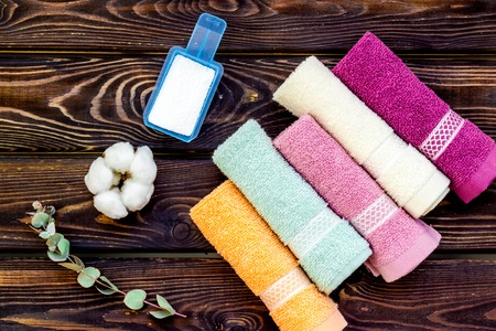 Products of cotton set. Preparing for laundry with washing powder and towels on wooden background top view