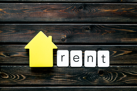 Rent house concept. Rent copy with house figure on wooden background top view