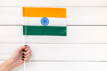 Symbol of the national day of India concept with flag in hand on white wooden background top view