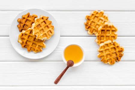 Hot homemade breakfast. Traditional Belgian waffles with honey on served white wooden table background top view