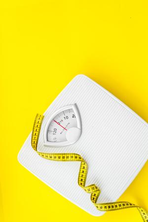 Nutrición apropiada. Hambruna médica. Concepto delgado con escala y cinta métrica en maqueta de vista superior de fondo amarillo