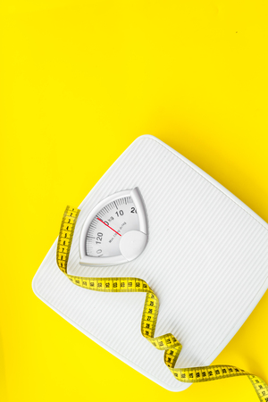 Proper nutrition. Medical starvation. Slim concept with scale and measuring tape on yellow background top view mockup 免版税图像