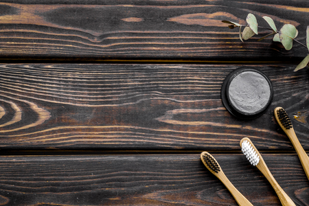 Zero waste lifestyle concept. Dental care with eco friendly bamboo tooth brush and carbon toothpaste on wooden background top view space for text Stock Photo