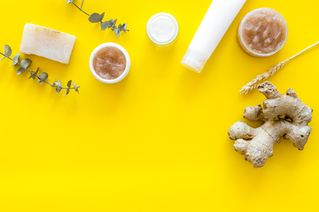 Body treatment. Cosmetics with natural herbal, ginger and wheat ingredients on yellow background top view copyspace Archivio Fotografico