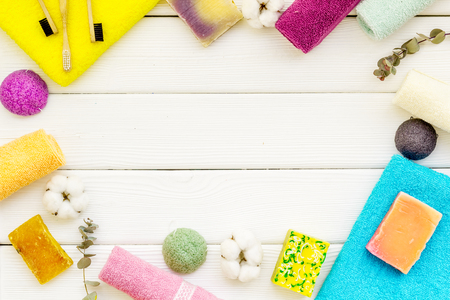 Soap, tooth brush, bath bomb. Spa or resort cosmetics and cotton towels to take bath frame on white wooden background top view space for text 版權商用圖片