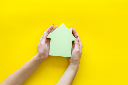 Property insurance concept. Buy house with house figure in hands on office desk yellow background top view