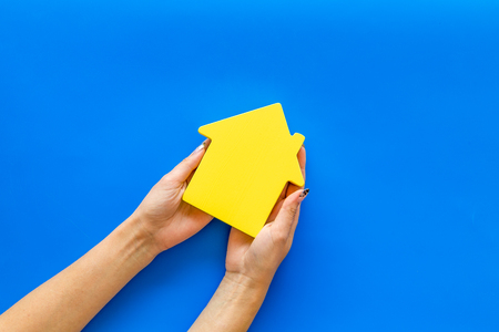 Property insurance concept. Buy house with house figure in hands on office desk blue background top view