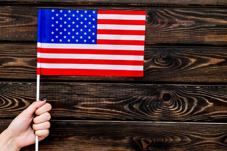 National day of USA concept with flag in hand on wooden background top view