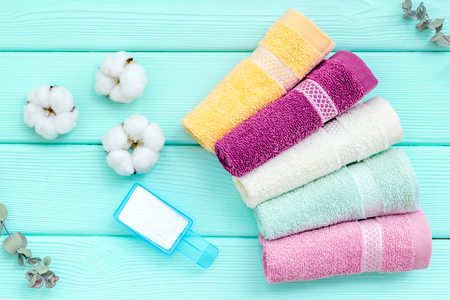 Products of cotton set. Preparing for laundry with washing powder and towels on mint green wooden background top view