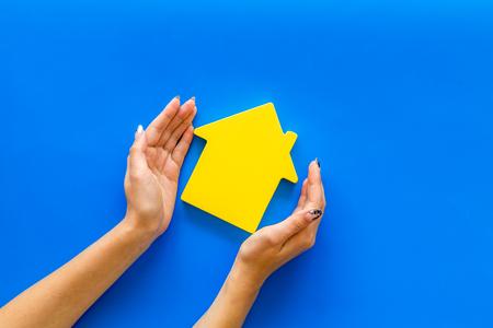 Suche nach einem neuen Hauskonzept mit Hausfigur in Händen auf blauem Schreibtischhintergrund Standard-Bild