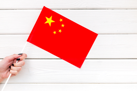 Independence Day of China concept with flag in hand on white wooden background top view. 版權商用圖片