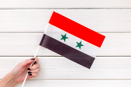 Symbol of the national day of Syria concept with flag in hand on white wooden background top view