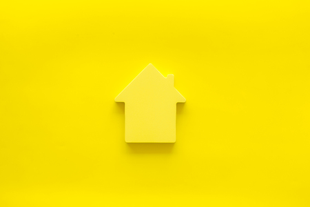 New house purchase. Property insurance concept with house toy on yellow background top view Stock Photo - 123908087