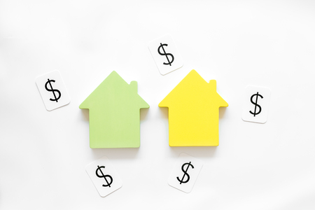 Property insurance concept. Buy house with house figure and dollar signs on office desk white background top view Stock Photo