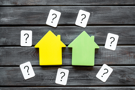 Search for a new house concept with house figure and question mark on wooden office desk background top view. Foto de archivo