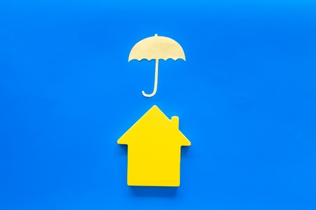Buy and insure house concept. Insurance concept with house figure and umbrella on blue background top view Stock Photo