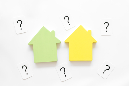 Search for a new house concept with house figure and question mark on white office desk background top view.