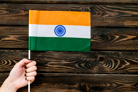 Independence Day of India concept with flag in hand on wooden background top view.