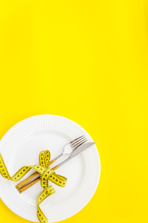 Slim. Medical starvation. Diet concept with plate, flatware and measuring tape for weight loss on yellow background top view mock up Фото со стока