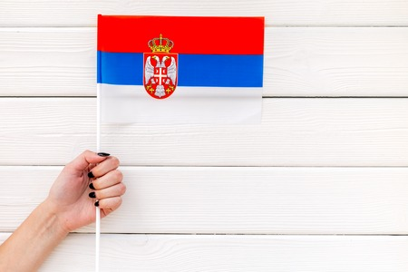 Flag of Serbia in hand on white wooden background top view. Banco de Imagens