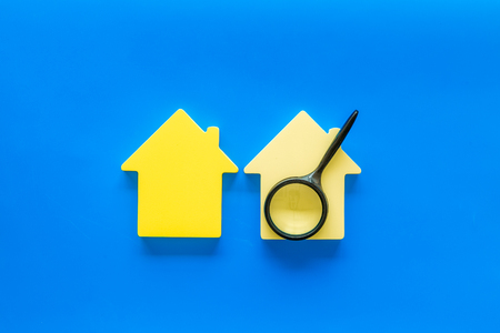 Buy house with house figure and magnifier on office desk blue background top view