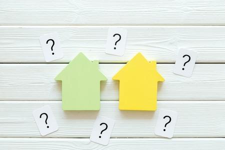 Concepto de crédito hipotecario con casa de juguete y signo de interrogación en el espacio de vista superior de fondo de madera blanca para texto
