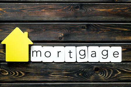 Mortgage copy with house figure on wooden background top view Stock Photo