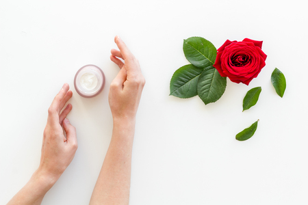 Natural floral cosmetics with rose flowers for face and body care in hands on white background top view Imagens