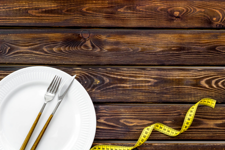 Diet concept with plate, flatware and measuring tape for weight loss on wooden background top view mock up Фото со стока