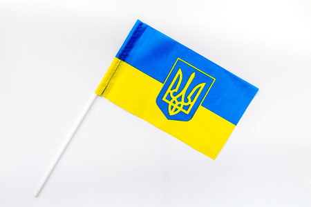 Flag of Ukraine in hand on wooden background top view