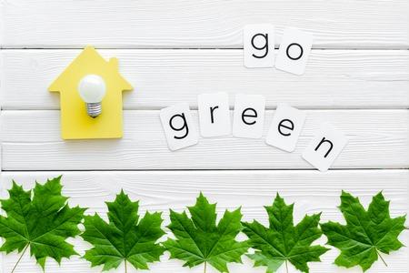 Vai al concetto verde con foglie di acero, casa e lampada su sfondo di legno bianco vista dall'alto Archivio Fotografico