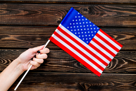 Flag of USA in hand on wooden background top view
