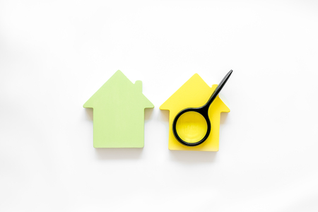 Search for a new house concept with house figure and magnifier on white office desk background top view Stock Photo