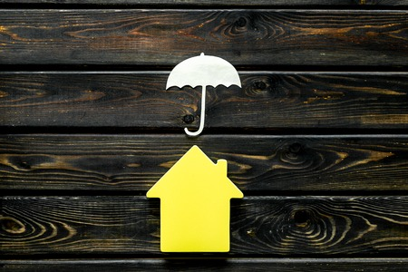 Insurance concept with house figure and umbrella on wooden background top view Stock Photo