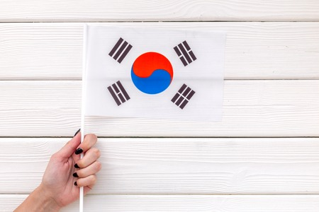 National day of South Korea concept with flag in hand on white wooden background top view
