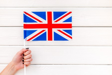Flag of United Kingdom of Great Britain in hand on white wooden background top view